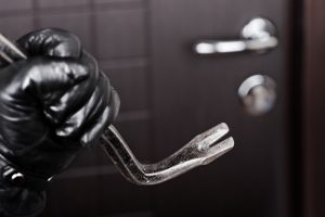 2445865-burglar-hand-holding-crowbar-break-opening-door